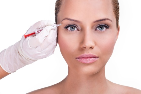 Beautiful woman gets botox injection in her face, correction upper lids Stock Photo