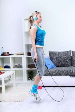saltar la cuerda: Mujer joven que usa una cuerda de saltar en casa