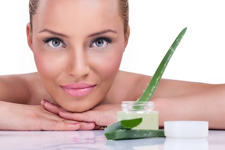 DERMATOLOGY:  Beautiful woman with healthy skin posing next cream of aloe vera