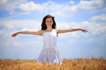 stretched out: Woman with arms stretched out in wheat field