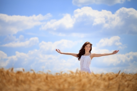 arm outstretched:  Woman  standing with outstretched arms in wheat field , freedom concept