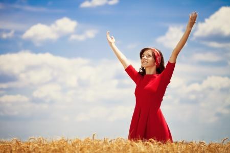manos levantadas al cielo: La felicidad mujer joven que se coloca en campo de trigo.