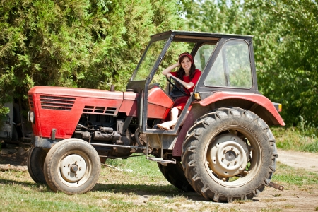 Young country girl on tractor, countryside photo