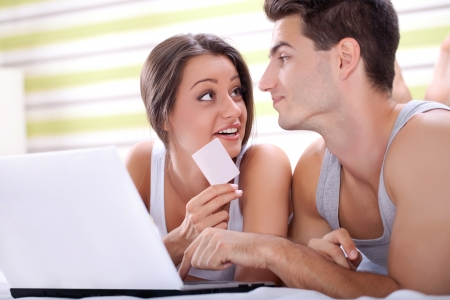Loving couple shopping over internet with credit card from bedroom photo