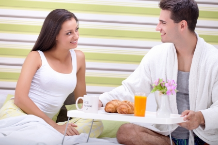 Young couple with breakfast in bed photo