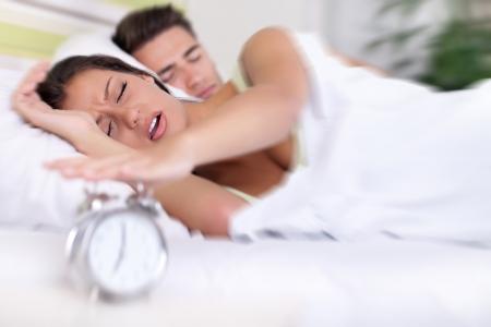 turn off: Upset woman turn off alarm clock, Wake up early morning. Stock Photo