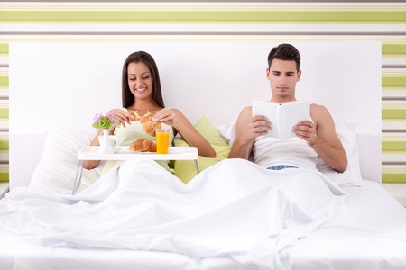 Young  couple on bed , woman having breakfast and man reading book  photo