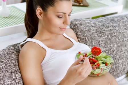 woman pregnant: Beautiful healthy pregnant woman  eating vegetable salad