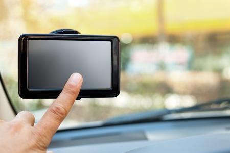navigation:  finger pointing at car GPS navigation system