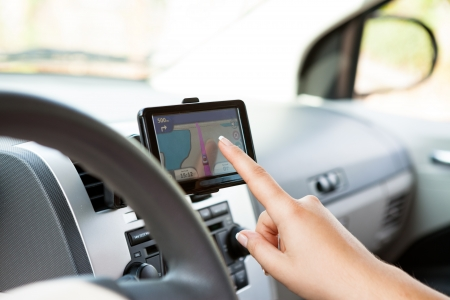 mapping:  GPS navigation panel on dashboard inside a car. Finger pointing on destination point. Stock Photo