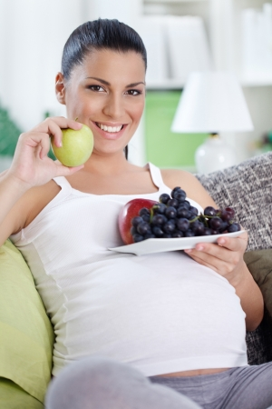 expectant:  Pregnant woman eating fruits, holding plate with fruits in belly