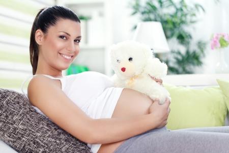 embarazada feliz: Sonriente mujer embarazada acostado en el sofá con osito de peluche