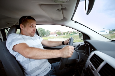 inhibit: Scared man driving car very fast,  focused on the drivers face Stock Photo