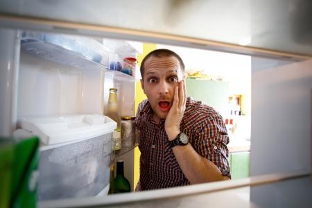 frigo: Geschokt mannen zoekt in zijn lege koelkast Stockfoto