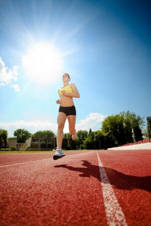 atleta corriendo: Mujer joven que se ejecuta en una pista.