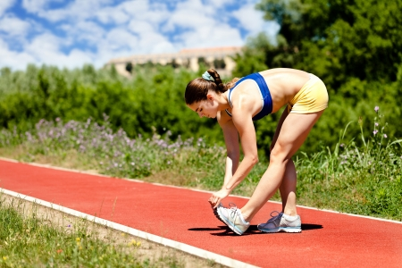 Young woman stretching on track. photo