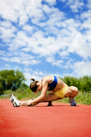 Sporty woman stretching legs photo