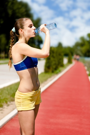 Young thirsty woman drinking water,  hydrating after training photo