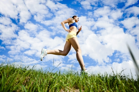 woman running: Young woman running outdoor over blue sky