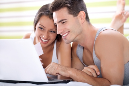 Happy young couple shopping online while lying on their bed photo