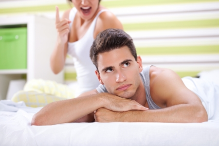 indifferent:  Couple in bedroom  having conflict, indifferent men in focus