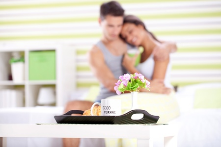 Happy couple having breakfast in bed, enjoying in morning  photo