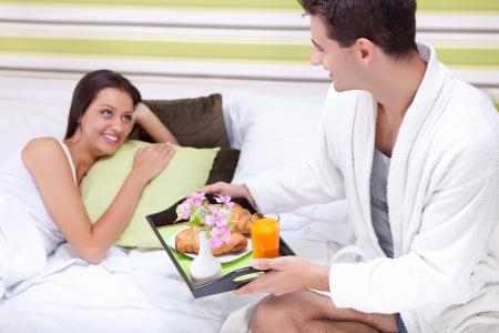 sleepwear:  Man bringing breakfast on tray to smiling woman in bed