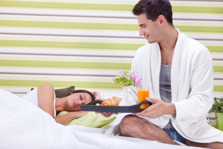Young man bringing breakfast in bed his sleeping wife  photo