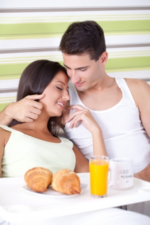 Affectionate couple having breakfast in bed, morning in bed  photo