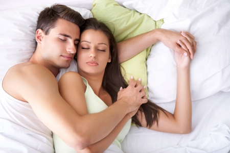 Embracing young couple sleeping on the bed photo