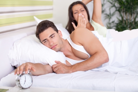 early morning: Morning. Young couple in bed. A man wants to turn off the alarm
