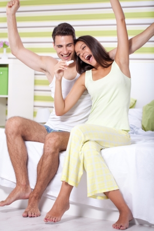 young happy couple with pregnancy test in bedroom  photo