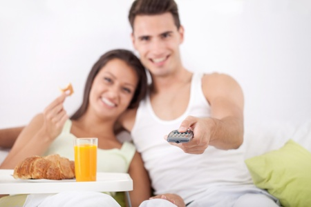 Young love couple having breakfast and watching TV in bed  photo