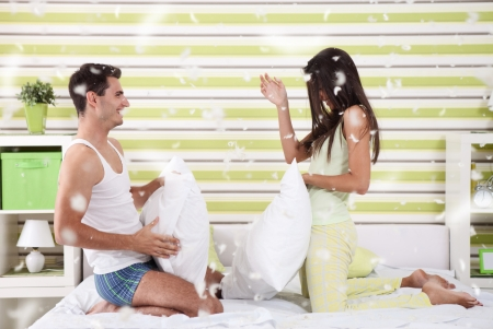 happy couple fighting with pillows in bed photo