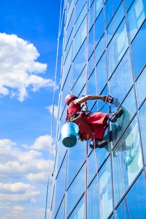 cleaning window: Lavavetri al lavoro e riflettono il cielo nelle finestre Editoriali