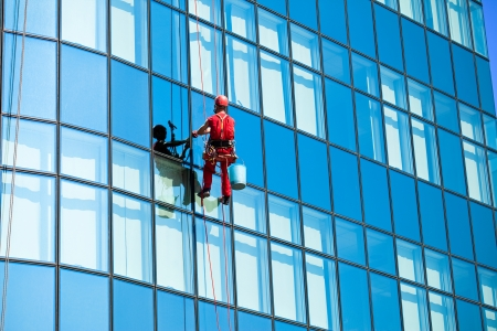 blue facades sky:  Washer wash the windows on  high office building