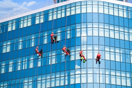 cleaning team: Cinco limpiadores de ventanas de edificio moderno Editorial