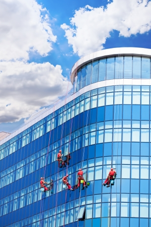 cleaning team: Trabajadores lavar ventanas en el edificio de oficinas
