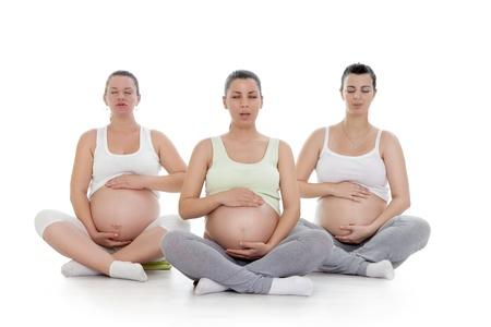 mujeres embarazadas: Tres mujeres embarazadas haciendo yoga y respiraci�n ejercicio Foto de archivo