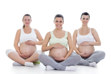 Group of smiling pregnant women doing prenatal yoga photo