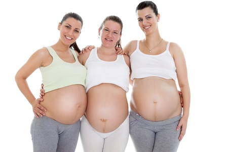 three young happiness pregnant women, standing and embracing  photo