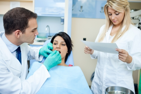 specialists: dentist and a nurse  curing teeth of female patient