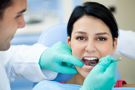 dental clinic: Female patient having her teeth examined by dental specialist