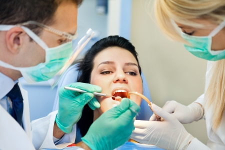 dentist at work:  female patient with open mouth receives an injection at the dentist