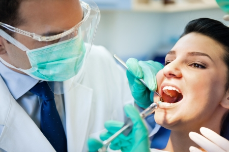 male dentist:  female patient with open mouth receives an injection at the dentist