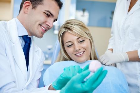 comunicacion oral: Dentista que muestra paciente le muestra los dientes o pr�tesis en el dentista Foto de archivo