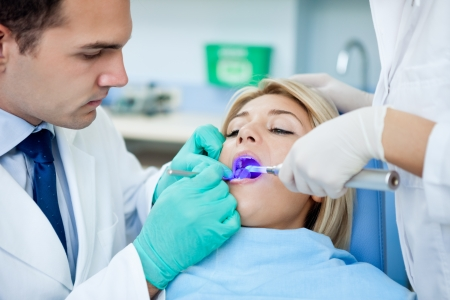 dentistry:  patient with open mouth receiving dental filling drying procedure. Stock Photo