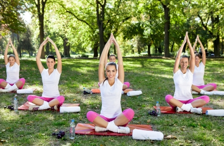 joga: group of six women practicing yoga in park