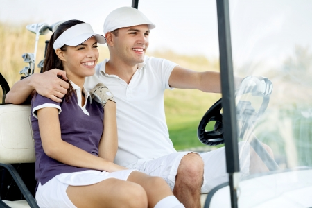 Golf couple driving in golf cart photo