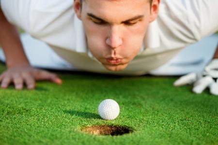 Golfer liegt auf dem Gras und Blasen in der Kugel, brauchen nur, um ihm ein wenig Hilfe. Lizenzfreie Bilder